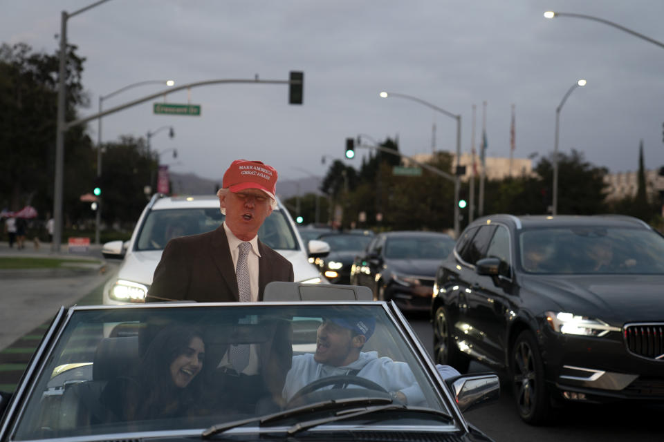 Two supporters of President Donald Trump laugh while sitting in a car with a cutout of Trump at a rally in Beverly Hills, Calif., Saturday, Oct. 24, 2020. (AP Photo/Jae C. Hong)