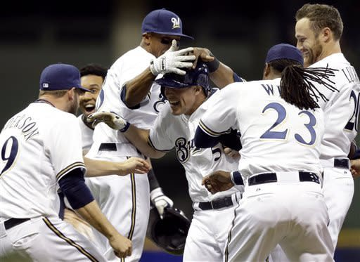 Milwaukee Brewers' Blake Lalli is mobbed by teammates after hitting a game-winning walk off single during the ninth inning of a baseball game against the San Francisco Giants Wednesday, April 17, 2013, in Milwaukee. The Brewers won 4-3. (AP Photo/Morry Gash)