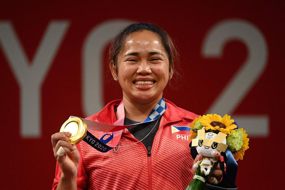 Gold medallist Philippines' Hidilyn Diaz stand on the podium for the victory ceremony of the women's 55kg weightlifting competition during the 2020 Tokyo Olympics.