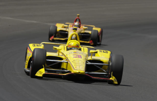 Helio Castroneves, of Brazil, leads Ryan Hunter-Reay through the first turn during the Indianapolis 500 auto race at Indianapolis Motor Speedway, in Indianapolis Sunday, May 27, 2018. (AP Photo/AJ Mast)