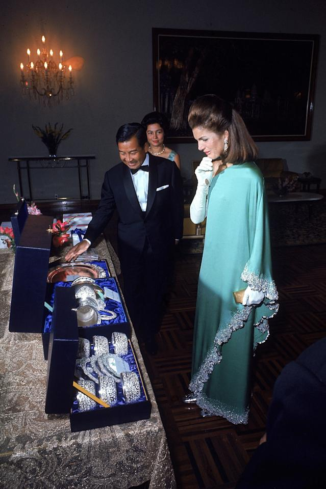 Jackie Onassis pictured receiving a gift from Prince Sihanouk of Cambodia and his wife during a trip to Cambodia in 1967. She dons a teal one-shoulder dress with decorative trim. Photo courtesy of Getty Images.