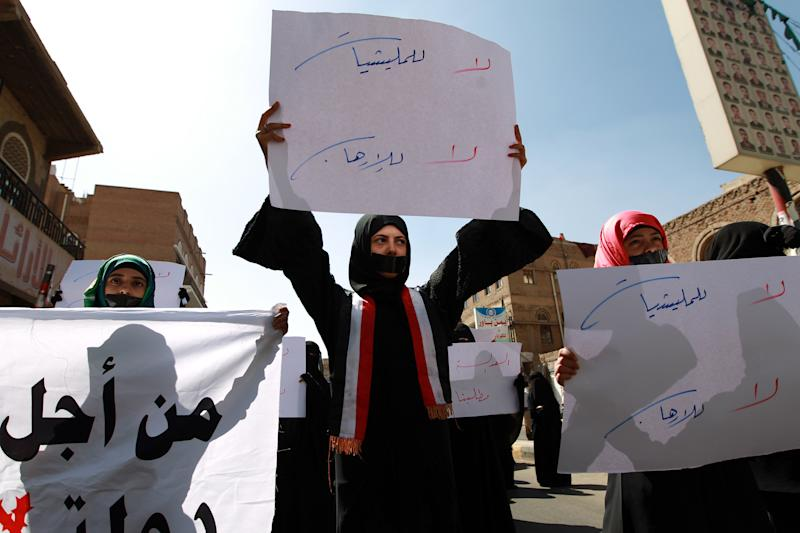 Yemeni activists with tape over their mouths carry placards during a rally in Sanaa, on November 8, 2014, against the control by Shiite Huthi fighters of the country's main cities