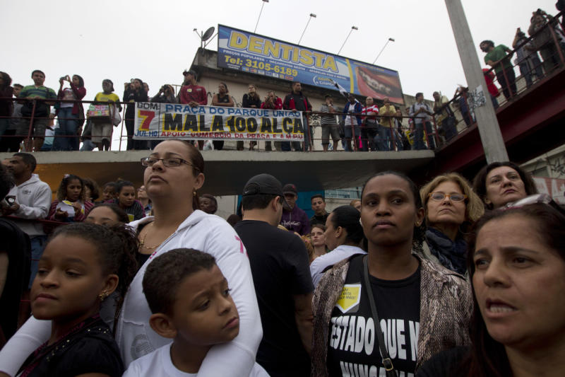 Residents hold a minute of silence in honor of people killed during a police operation last in the Mare slum, in Rio de Janeiro, Brazil, Tuesday, July 2, 2013. The police operation aimed to capture an alleged looter, who according to police killed an officer after a peaceful protest. At least nine people died and two suspects were captured during the June 25th operation, according to the police. (AP Photo/Silvia Izquierdo)