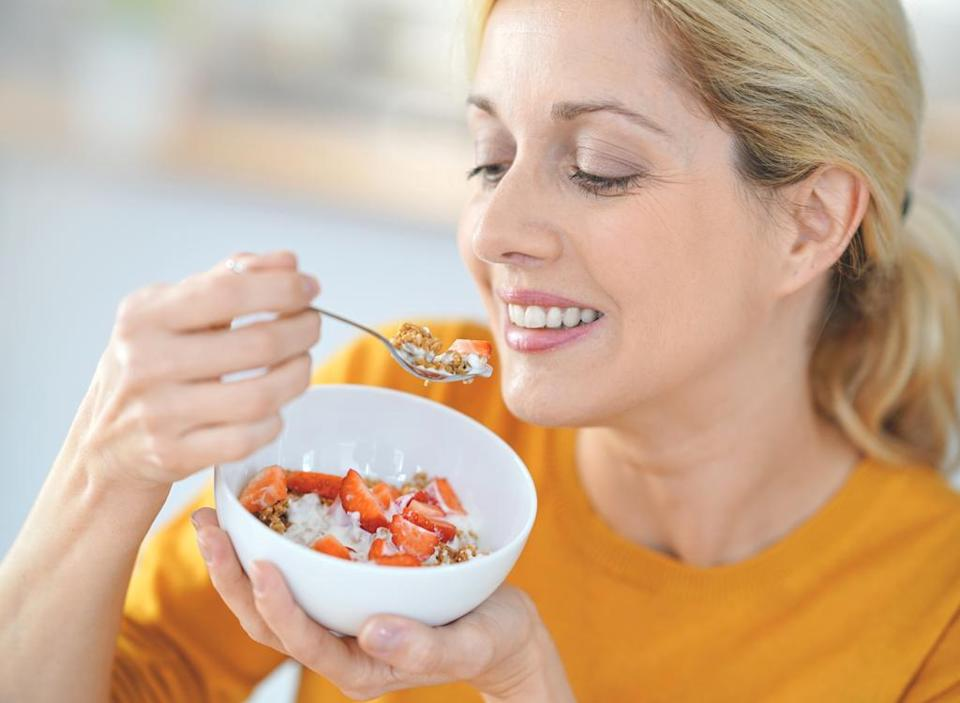 Woman eating breakfast yogurt