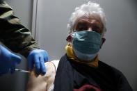 Michalis Tzouanos, 76, receives the second dose of Moderna COVID-19 vaccine at Promitheas vaccination mega center in Athens, Friday, March 19, 2021. More than 1.35 million doses of the COVID-19 vaccine have been administered so far in Greece, but daily infections remain on the rise despite four months of lockdown measures. (AP Photo/Thanassis Stavrakis)