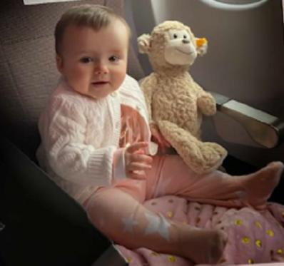 Phoebe Moon is pictured with a toy monkey in a plane seat.
