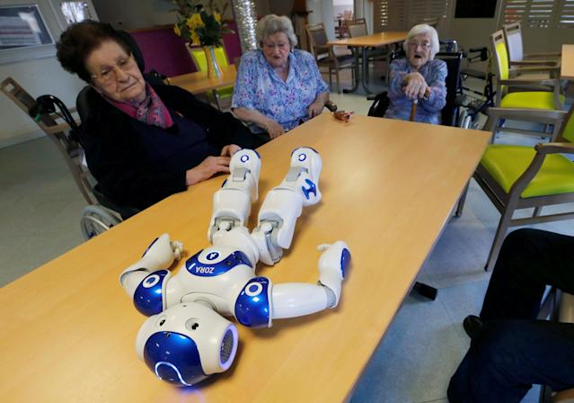 Elderly people play with a robot named NAO, manufactured by Softbank Robotics, in their retirement home in Bordeaux, France, March 16, 2018. REUTERS/Regis Duvignau TPX IMAGES OF THE DAY