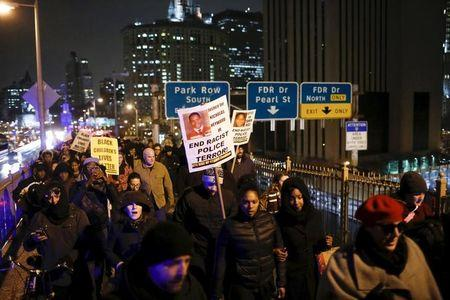 People march along the Brooklyn Bridge as they take part in a protest against the police in Manhattan
