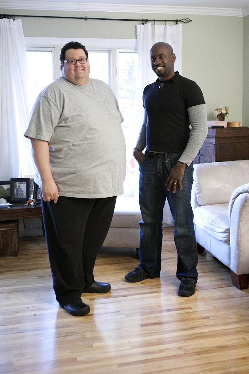"This Oct. 25, 2011 photo courtesy of Food Network shows chef Michael Mignano, left, as he poses for a portrait with health consultant Robert Brace at his home in Bayport, N.Y., as seen on Food Network's ""Fat Chef."" At 6-2, Mignano weighed about 500 pounds soon after he was diagnosed with Type 2 diabetes in 2010, before ""Fat Chef"" went into production last October. (AP Photo/Food Network)"
