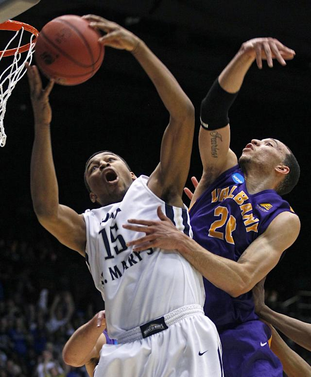 Mount St. Mary's forward Gregory Graves (15) pulls a rebound away from Albany forward Gary Johnson in the first half of a first-round game of the NCAA college basketball tournament, Tuesday, March 18, 2014, in Dayton, Ohio. (AP Photo/Skip Peterson)