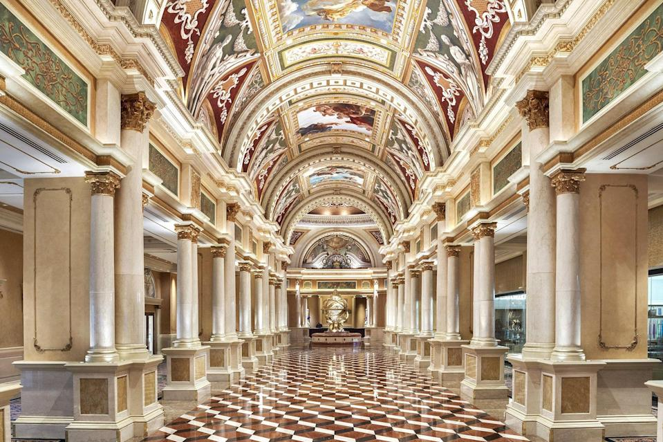 """<p><strong>How did it strike you on arrival?</strong><br> When you walk into The Venetian lobby, it's completely frescoed to its vaulted ceiling, and its centerpiece is a massive gilded sphere held up by four golden women. After having passed a replica of Venice's campanile and Rialto Bridge, arriving in this basilica-style registration area should feel totally cheesy....and yet, it is SO over-the-top and grand, you can't help but be impressed. Yes, even if you have actually been to real Venice. The Venetian and its sister tower, <a href=""""https://www.cntraveler.com/hotels/united-states/las-vegas/the-palazzo?mbid=synd_yahoo_rss"""" rel=""""nofollow noopener"""" target=""""_blank"""" data-ylk=""""slk:The Palazzo"""" class=""""link rapid-noclick-resp"""">The Palazzo</a>, are both a part of The Venetian Resort.</p> <p><strong>What's the crowd like?</strong><br> The Venetian and Palazzo complex is so enormous—more than 7,000 rooms and three million square feet of retail and meeting space, there's absolutely no way to categorize the travelers you see at this hotel. They run the gamut from conventioneers of all kinds to people who know and love the Venetian, to people checking in to the massive Canyon Ranch that spans both hotels.</p> <p><strong>The good stuff: Tell us about your room.</strong><br> The Venetian has made much of how all of its rooms are suites. They are all quite large (the standard size is 650 square feet, and they go up from there). Especially if you are here on business, the step down in each room from sleeping area to a small living room, with desk and big flat screen television, makes a huge psychological difference. All of the suites have been recently refreshed, too, to keep pace with Strip-wide renovations. I've stayed in both a Luxury Suite (the standard, with a king-sized bed) and a Bella Suite (essentially the same layout, slightly larger, with two queens). All done with cream-colored walls and neutral carpets but with jewel-toned accent chairs, they're more modern and def"""