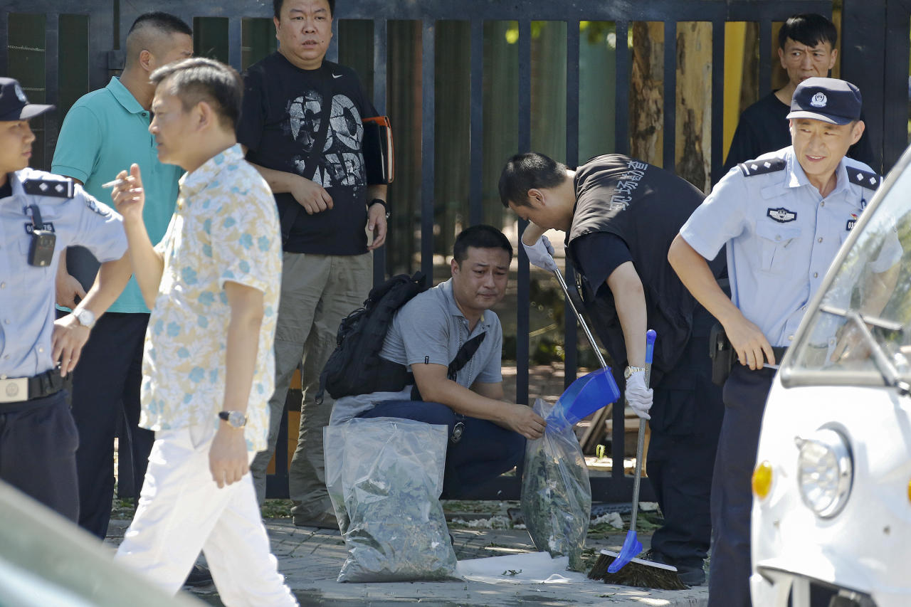 <p>Crime scene police put tree leaves into a bag near the blast site outside the U.S. Embassy in Beijing, Thursday, July 26, 2018. (Photo: Andy Wong/AP) </p>