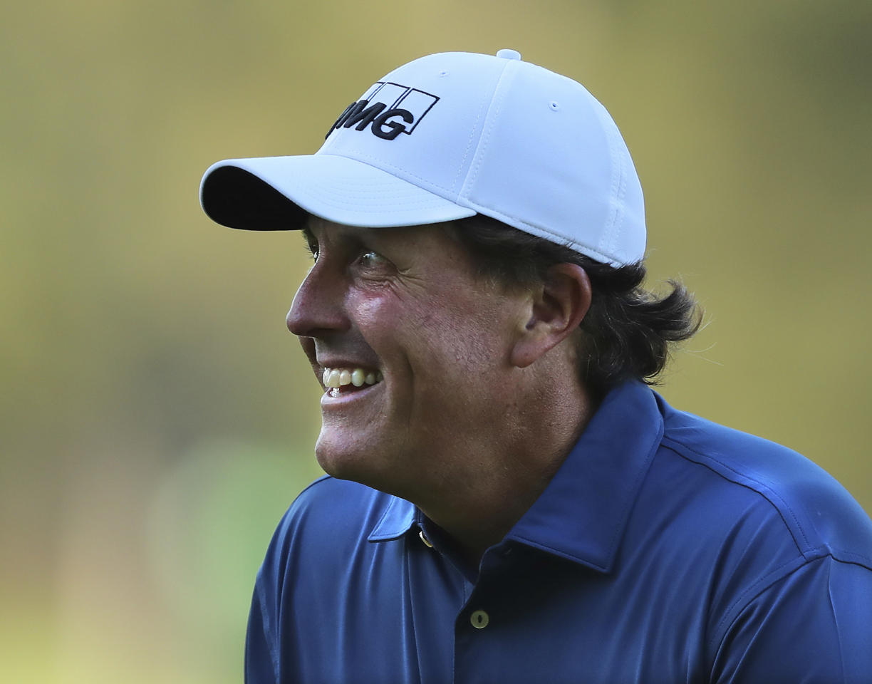 """FILE - This April 4, 2017 file photo shows Phil Mickelson smiling after chipping in for an eagle on the third hole during a practice round at the Masters golf tournament in Augusta, Ga. Mickelson isn't sure what's next for Jim """"Bones"""" Mackay. He is sure there are going to be plenty of options for his longtime caddie. Mickelson and Mackay announced last week they had decided to split up after 25 years and more than 600 tournaments around the world, ending one of golf's most successful relationships. (Curtis Compton/Atlanta Journal-Constitution via AP)"""