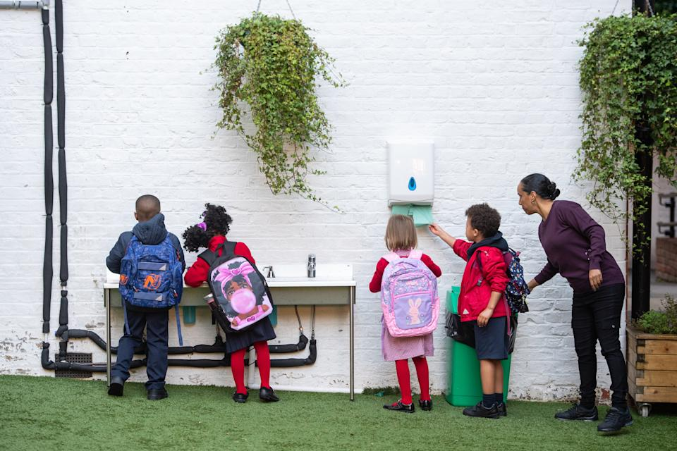 Pupils wash their hands as they arrive on the first day back to school at Charles Dickens Primary School in London, as schools in England reopen to pupils following the coronavirus lockdown. Approximately 40% of schools are expected to welcome back students for the start of the autumn term today, despite concerns being raised about their ability to reopen safely.