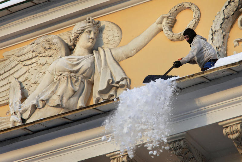 Municipal worker cleans snow from the roof of Aleksandriysky theatre in St. Petersburg, Russia, Tuesday, Nov. 30, 2010. The temperature in St.Petersburg is around -12 C (10 F). (AP Photo/Dmitry Lovetsky)