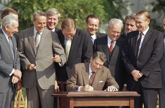 Lawmakers look on as President Ronald Reagan signs into law a landmark tax overhaul on the South Lawn of the White House,Oct. 22, 1986. (Photo: AP)