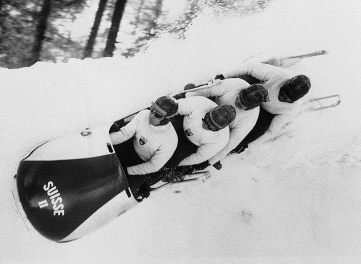 "FILE - In this Feb. 4, 1956, file photo, a shower of snow and ice from the number two Swiss bobsled sprays over the banked edge of the bumpy Olympic bobsled course of Cortina D'Ampezzo, Italy, as Max Angst battles for control of the speeding four-man sled. The Cortina track was built in 1923 and the resort known as the ""Queen"" of the Italian Dolomites was home to bobsledding great Eugenio Monti, who won six Olympic medals between 1956 and 1968. (AP Photo/Jim Pringle, File)"