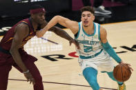Charlotte Hornets' LaMelo Ball (2) drives past Cleveland Cavaliers' Damyean Dotson during the second half of an NBA basketball game, Wednesday, Dec. 23, 2020, in Cleveland. (AP Photo/Tony Dejak)