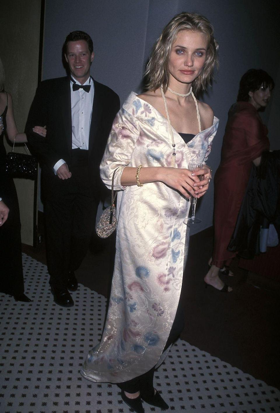 """<p>At the 1999 Golden Globes Awards after-party, Cameron was like, """"listen, I'm going to show you <em>exactly</em> how '90s I can go."""" That has to be the explanation for this long kimono style dress over black pants (pants?!), grungy hairstyle and makeup, and long pearls. <br></p>"""