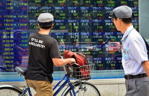 <p>Pedestrians look at an electric quotation board flashing the Nikkei key index of the Tokyo Stock Exchange (TSE) on September 9, 2013. Japanese stocks jumped nearly three percent in opening trade on September 9 as investors cheered Tokyo winning its bid to host the 2020 Olympics.</p>