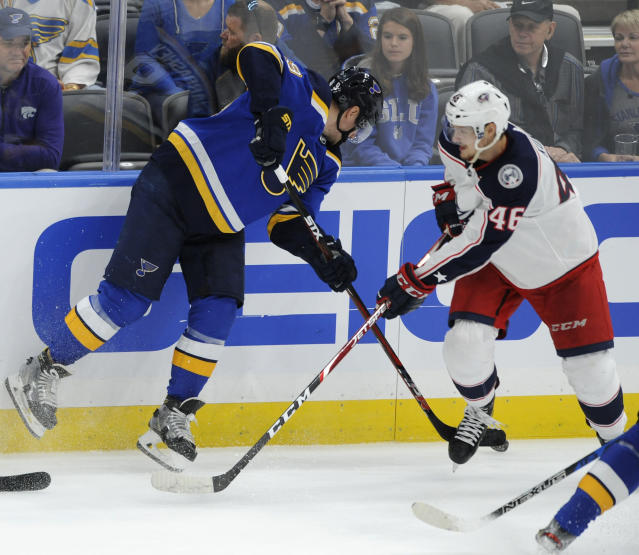St. Louis Blues' Ivan Barbashev, left, of Russia, reaches for the puck against Columbus Blue Jackets' Dean Kukan (46), of Switzerland, during the third period of an NHL preseason hockey game, Sunday, Sept. 22, 2019, in St. Louis. (AP Photo/Bill Boyce)