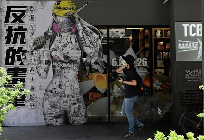 A woman in Taipei walks past a billboard promoting democracy for Hong Kong (AFP Photo/Sam Yeh)