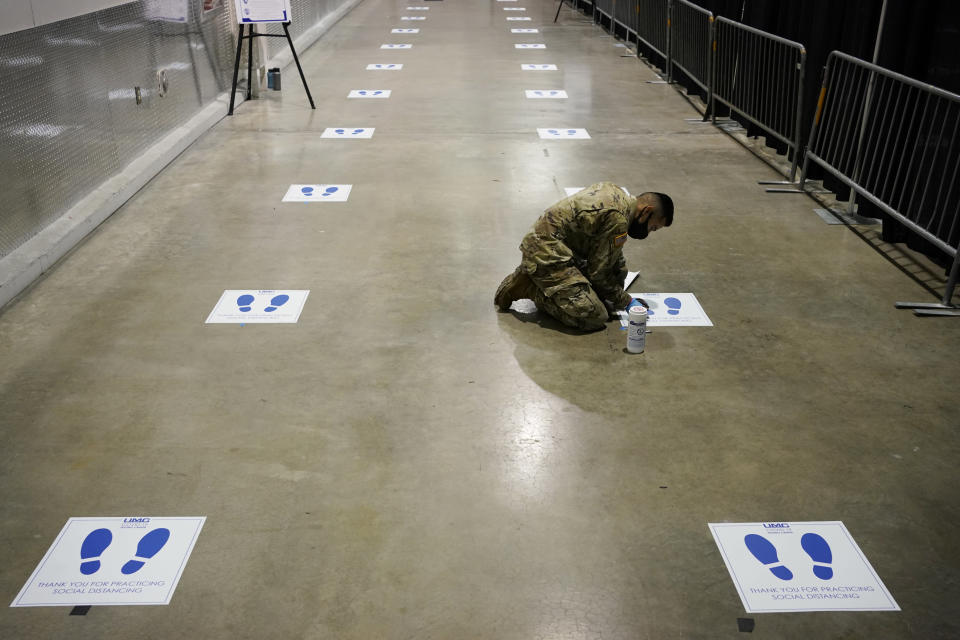 A member of the Nevada National Guard installs social distancing stickers while setting up a new temporary coronavirus testing site Monday, Aug. 3, 2020, in Las Vegas. (AP Photo/John Locher)