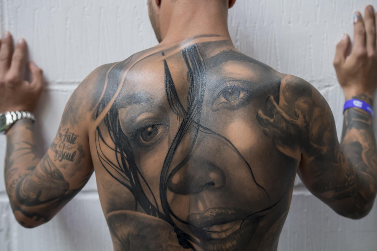 <p>A visitor shows his tattooed back at the London Tattoo convention at Tobacco Dock on Sept. 23, 2017 in London, England. Over 400 tattoo artists are attending the three day event in East London to showcase their artistry and for visitors to see and have tattoos done for themselves. (Photo: James D. Morgan/Getty Images) </p>