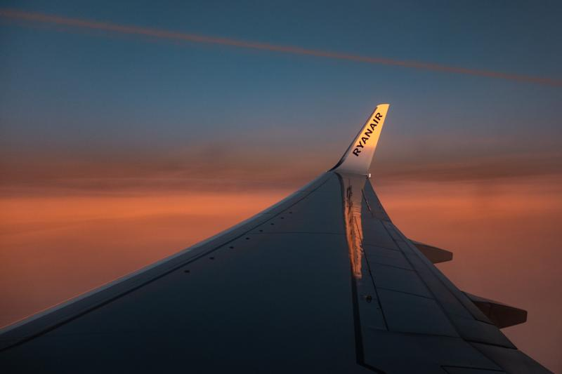 Wing view from the window of an airliner during the magic hour after the sunset. The aircraft is a Boeing 737-800 of the low-cost airline, Ryanair. (Photo by Nicolas Economou/NurPhoto via Getty Images)
