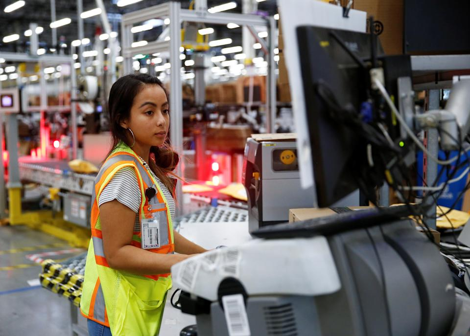 Employee Stanaleen Greenman works on processing packages kicked out by the automated scanning and labeling system at the Amazon fulfillment center in Kent, Washington, U.S., October 24, 2018.  REUTERS/Lindsey Wasson