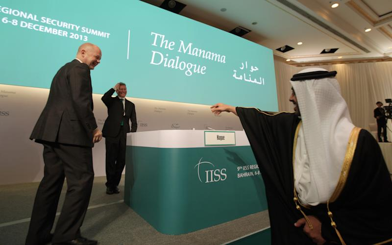 Emirati Foreign Minister Abdullah bin Zayed Al Nahyan, right, greets British Foreign Secretary William Hague, left, as Hague approaches the podium to address the opening of the International Institute of Strategic Studies (IISS) conference in Manama, Bahrain, on Friday, Dec. 6, 2013. At center is IISS director-general John Chipman. The IISS Manama conference is expected to discuss regional security issues including the recently reached deal on Iran's nuclear program. (AP Photo/Hasan Jamali)