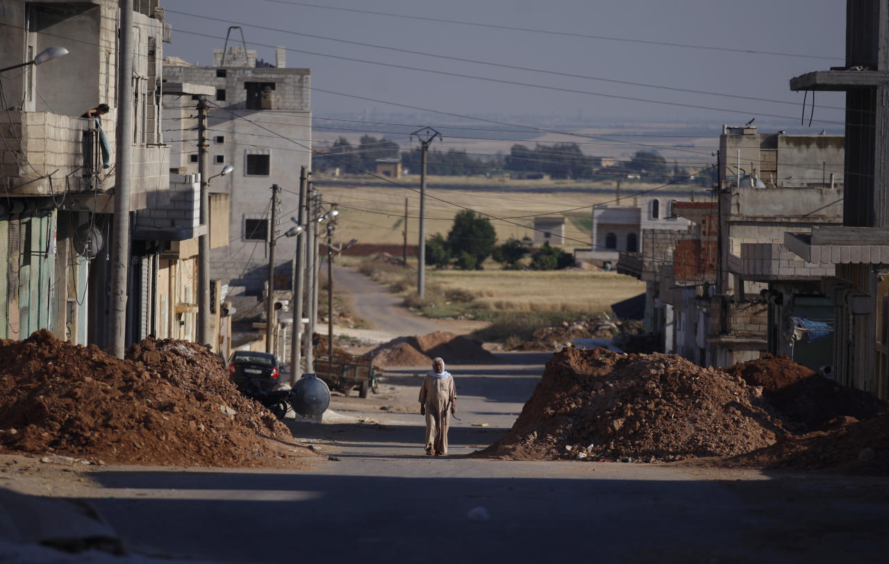 FILE - In this Tuesday, June 5, 2012 file photo, a Syrian man walks between piles of dirt left by the Syrian army on the sides of a street in the town of Taftanaz, 15 kilometers east of Idlib, Syria. At dawn on April 3, Syrian forces shelled the town in the first volley of what residents say was a massive assault after a string of large protests calling for the end of the autocratic rule of President Bashar Assad. (AP Photo/Khalil Hamra, File)