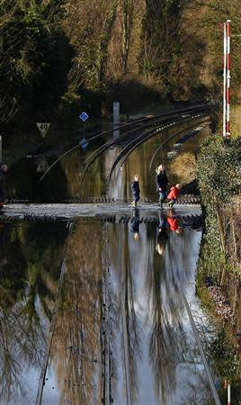 Residents are seen crossing the tracks after the river Thames flooded the railway in the village of Datchet, southern England February 10, 2014. REUTERS/Eddie Keogh