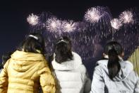 A fireworks display decorates the night sky to celebrate the New Year, as crowds of people look on, at Kim Il Sung Square in Pyongyang, North Korea, early Friday, Jan., 1, 2021. (AP Photo/Jon Chol Jin)