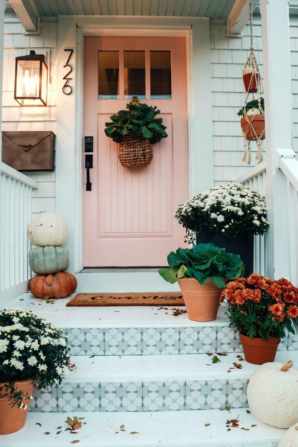 """<p>Sometimes creating a cozy outdoor pumpkin display is as simple as stacking your pumpkins and setting out a few potted plants. </p><p><strong>See more at <a href=""""https://nestingwithgrace.com/fall-front-porch-and-tile-front-steps/"""" rel=""""nofollow noopener"""" target=""""_blank"""" data-ylk=""""slk:Nesting With Grace"""" class=""""link rapid-noclick-resp"""">Nesting With Grace</a>. </strong></p><p><a class=""""link rapid-noclick-resp"""" href=""""https://www.amazon.com/Gresorth-Halloween-Decorative-Artificial-Decoration/dp/B019QKLX82?tag=syn-yahoo-20&ascsubtag=%5Bartid%7C2164.g.36877187%5Bsrc%7Cyahoo-us"""" rel=""""nofollow noopener"""" target=""""_blank"""" data-ylk=""""slk:SHOP WHITE PUMPKINS"""">SHOP WHITE PUMPKINS</a></p>"""