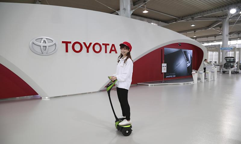 """A Toyota gallery staff member takes a ride on Toyota's electric personal mobility robot """"Winglet"""" in Tokyo Thursday, May 8, 2014. Toyota's fourth quarter profit dropped slightly despite higher vehicle sales and a weak yen as it spend more on research and development. Toyota Motor Corp. reported Thursday a January-March profit of 297 billion yen ($2.9 billion), down from 313.9 billion yen a year earlier. Quarterly sales rose 12.5 percent to 6.57 trillion yen ($64.5 billion). (AP Photo/Koji Sasahara)"""