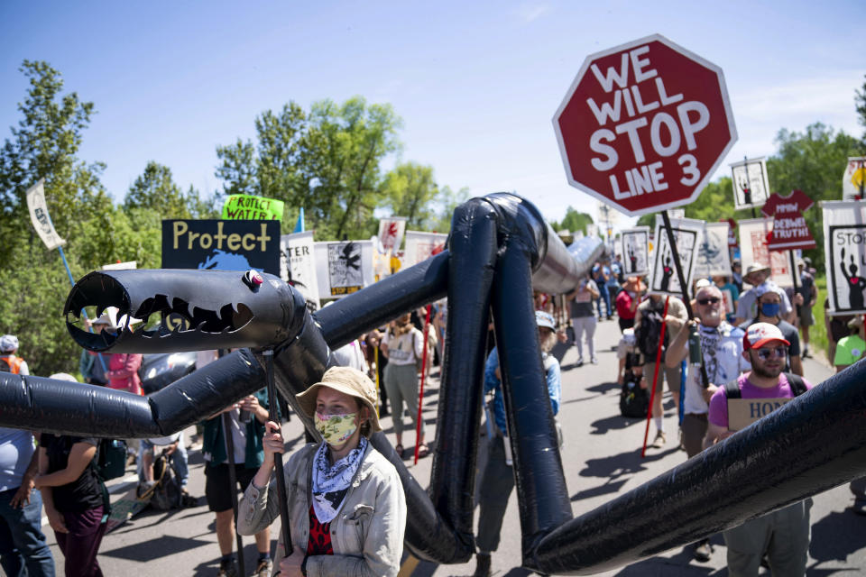 """A makeshift """"black snake"""" resembling a pipeline is carried as demonstrators march along Highway 9, on Monday, June 7, 2021, in Clearwater County, Minn. More than 2,000 Indigenous leaders and """"water protectors"""" gathered in Clearwater County from around the country to protest the construction of Enbridge Line 3. The day started with a prayer circle and moved on to a march to the Mississippi headwaters where the oil pipeline is proposed to be built. (Alex Kormann/Star Tribune via AP)"""