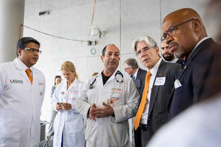 University of Miami President Julio Frenk, in orange tie, confers with, from left, Drs. Dipen Parekh, Tanira Ferreira, David Lang, UHealth Emergency Manager Vincent Torres, back right, and UM Miller School of Medicine Dean Henri Ford, right, on the medical campus as they discuss demand surge during the coronavirus pandemic.
