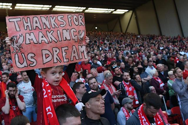 A young Liverpool fan holds up a sign thanking his team after their title bid came to a frustrating end (AFP Photo/Paul ELLIS)