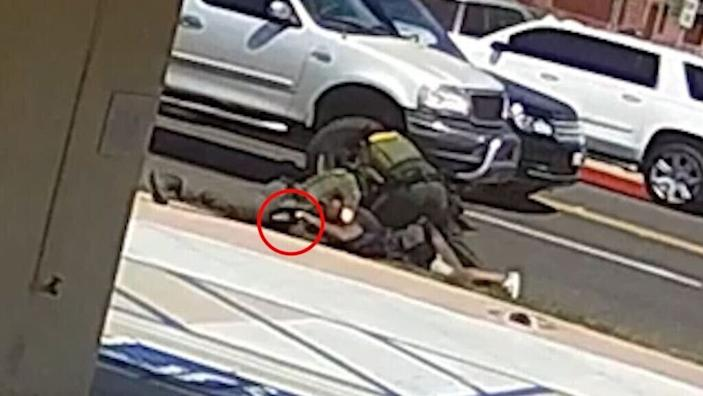 A still image from a security camera provided by the Orange County Sheriff's Department of the struggle between two deputies and a homeless Black man shot dead by one of the deputies. Sheriff Don Barnes said the red circle shows Kurt Reinhold hand on the deputy's gun.