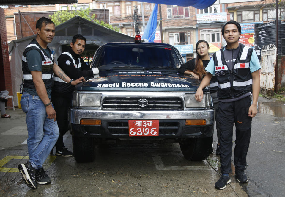 """Members of the RNA-16 volunteer group, from left, Arun Saiju, Rajesh Gaiju, Punam Karmacharya and Nhuja Kaiju stand for a photograph during an interview with the Associated Press at a hospital in Bhaktapur, Nepal, Tuesday, May 26, 2020. RNA-16 stands for """"Rescue and Awareness"""" and the 16 kinds of disasters they have prepared to deal with, from Nepal's devastating 2015 earthquake to road accidents. But the unique services of this group of three men and a woman in signature blue vests in the epidemic amount to a much greater sacrifice, said doctors, hospital officials and civic leaders. (AP Photo/Niranjan Shrestha)"""