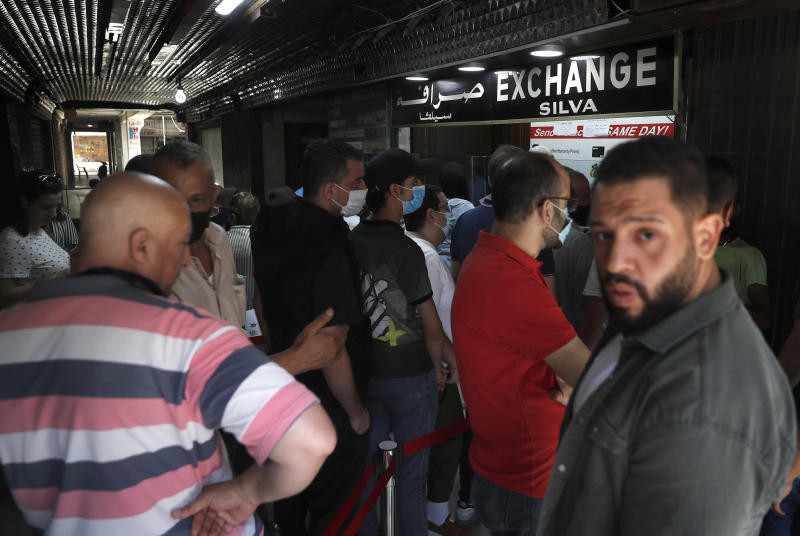 People line up outside an exchange shop to buy U.S. dollars, in Beirut, Lebanon,  June 17, 2020. Lebanon's financial meltdown has thrown its people into a frantic search for dollars as the local currency's value evaporates. Long, raucous lines mass outside exchange bureaus to buy rationed dollars. With tens of thousands thrown into poverty, the turmoil is fueling bitterness at banks and politicians. (AP Photo/Hussein Malla)