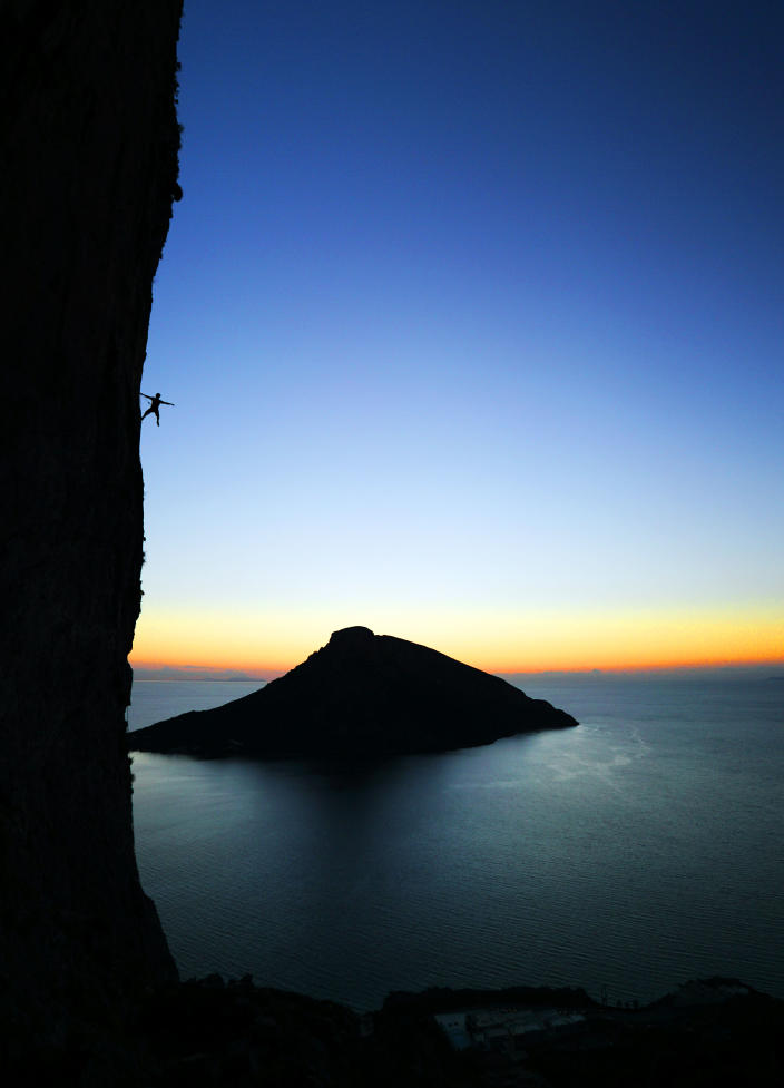 A climber poses on a rock during a climb in Kalymnos, Greece. (Photo: Adam Kokot/Caters News)
