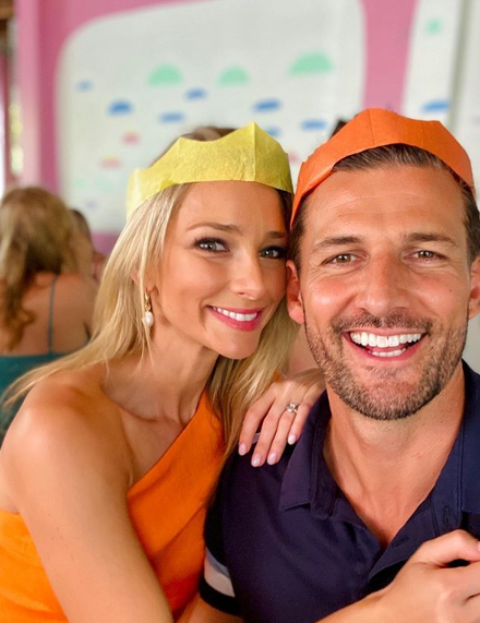 A photo of Anna Heinrich and Tim Robards wearing paper crowns at a family Christmas lunch.
