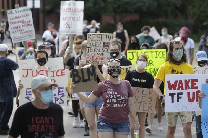 Demonstrators display placards during a protest held to call for an end to racial injustice, Sunday, Aug. 9, 2020, in Boston, triggered by the death of George Floyd, an African American man who died on May 25 as a Minneapolis police officer pressed his knee into his neck, ignoring his cries and bystander shouts until he eventually stopped moving. (AP Photo/Steven Senne)