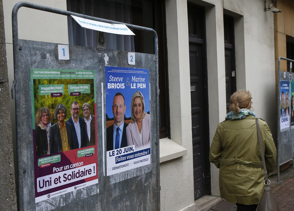 Electoral campaign boards for northern France region, right, with local candidate Steeve Briois and Marine Le Pen, French far- right leader, in Henin-Beaumont, northern France, Friday, June 25, 2021. Marine Le Pen's far right party is riding high on her tough-on-security, stop-immigration message as French voters start choosing regional leaders Sunday in an election that's seen as a dress rehearsal for next year's presidential vote. (AP Photo/Michel Spingler)