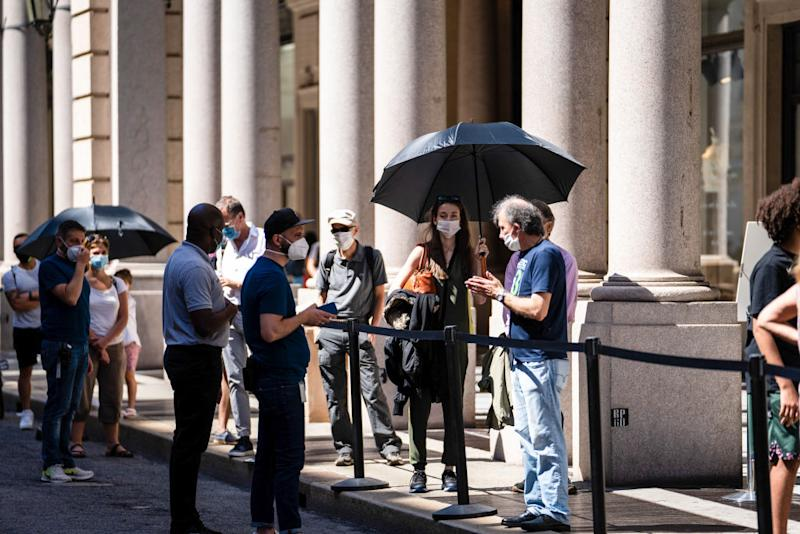 Pedestrians adopt a safe social distance as they stand in line outside an Apple Inc. store in Turin, Italy, on Tuesday, June 23, 2020. Italian Prime Minister Giuseppe Conte said his government would likely seek a wider budget gap as he draws up an ambitious reform plan to lobby for European Union assistance to restart the economy. Photographer: Federico Bernini/Bloomberg