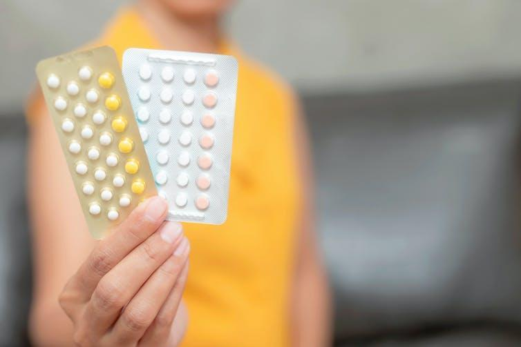 A woman holding two blister packs of oral contraceptive pills