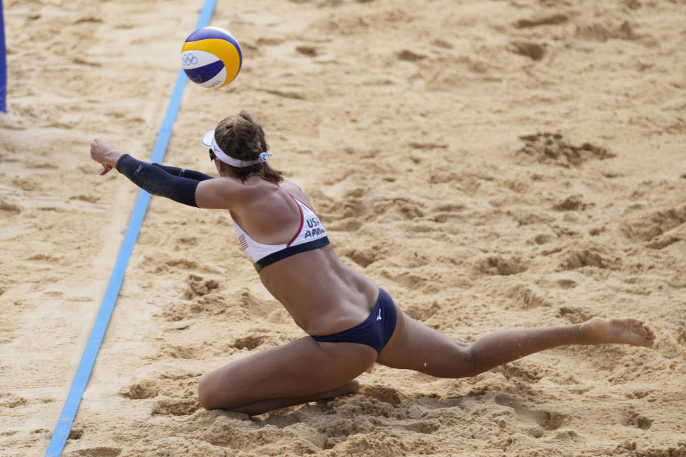 April Ross, of the United States, dives for a shot during a women's beach volleyball match against Germany at the 2020 Summer Olympics, Tuesday, Aug. 3, 2021, in Tokyo, Japan. (AP Photo/Felipe Dana)