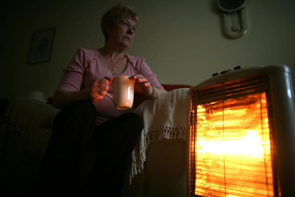 CONWY, UNITED KINGDOM - NOVEMBER 06:  In this photo illustration an old age pensioner keeps warm with the aid of an electric heater on November 6, 2008, in Conwy, Wales. With the recent high rise in fuel and energy bills many senior citizens are facing a cold winter. The UK's National pensioner Convention has called for a higher basic state pension for the over 60's.  (Photo by Christopher Furlong/Getty Images)